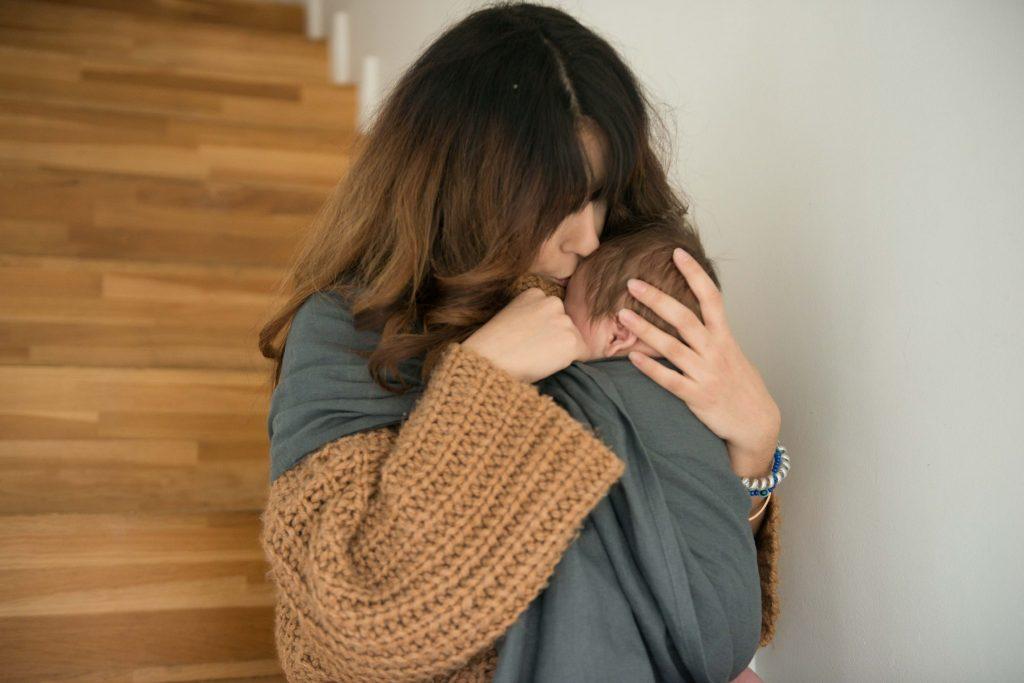 Kobieta trzymająca dziecko w chuście The Slings
