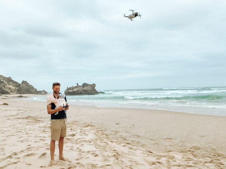 Mężczyzna lata dronem i trzymaja dziecko w chuście The Slings na plaży